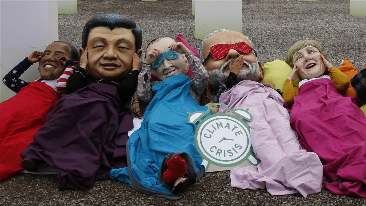Des militants de la lutte contre la pauvreté d'Oxfam affublés de masques représentants de grands leaders mondiaux à la conférence sur le climat à Paris