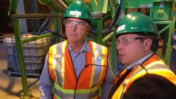 Jean-Claude Savoie (à gauche) et Chris Hooper dans une usine. Ils portent des dossars oranges et jaunes et un casque vert. Ils portent aussi des lunettes de sécurité.