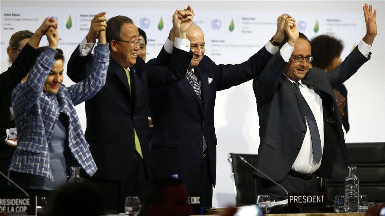 Christiana Figueres, secrétaire exécutive de la Convention-cadre des Nations unies sur les changements climatiques, Ban Ki-moon, secrétaire général des Nations unies, Laurent Fabius,  président de la conférence de Paris et ministre des Affaires étrangères de la France, et François Hollande, président français, célèbre la conclusion d'un accord sur le climat.