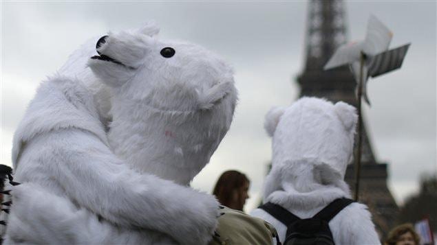 Des militants écologistes manifestent devant la tour Eiffel à Paris, le 12 décembre.
