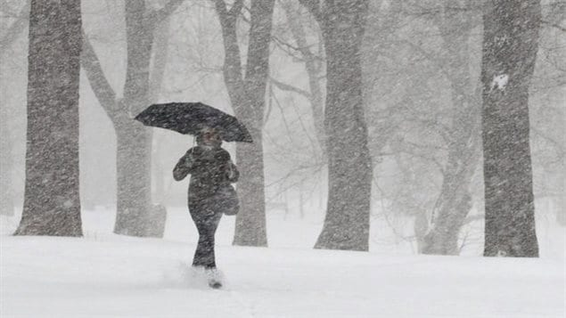 Une femme marche dans une tempête de neige