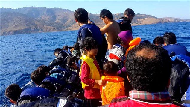 Des dizaines de réfugiés s'entassant dans des bateaux pneumatiques en chemin vers la Grèce. Des dizaines de réfugiés s'entassant dans des bateaux pneumatiques en chemin vers la Grèce. Parmi eux, le jeune réfugié afghan, Mohammed-Reza Rezaie.