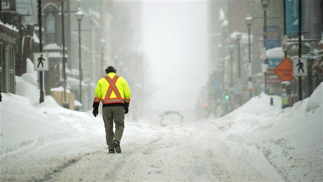 Un piéton marche en plein milieu de la rue au centre-ville d'Halifax durant une autre tempête de neige.