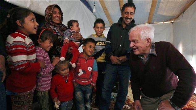 Le ministre John McCallum et des réfugiés syriens dans un camp, au Liban