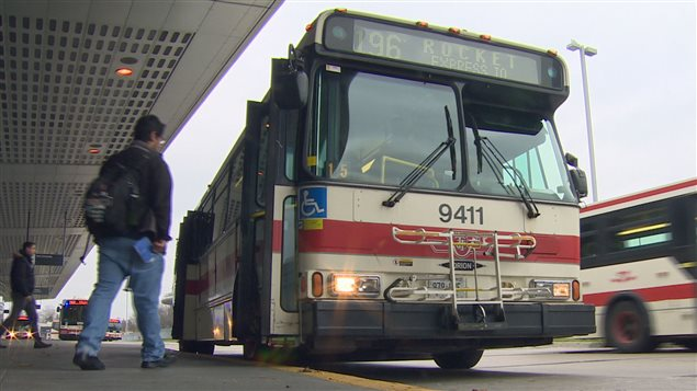 Des usagers s'apprêtent à monter à bord d'un autobus de la CTT à Toronto.