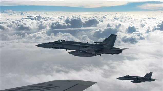 Royal Canadian Air Force CF-18 Hornets depart after refueling with a KC-135 Stratotanker assigned to the 340th Expeditionary Air Refueling Squadron, October 30, 2014, over Iraq.