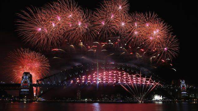 Des feux d'artifice explosent au-dessus de l'Opéra de Sydney et du Harbour Bridge, en Australie, pour fêter le Nouvel An, le 1er janvier 2016.