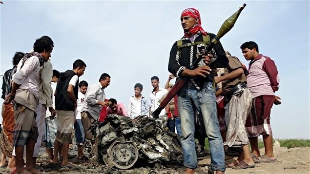 Un policier se tient devant une voiture qui a explosé dans un attentat à Aden au Yémen, le 5 janvier 2016.