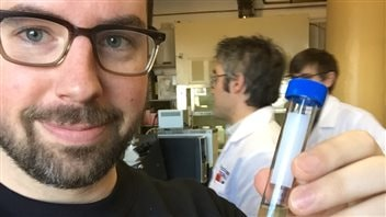 Chris Renolds montre une éprouvette contenant de la bière âgée d'environ 120 ans.