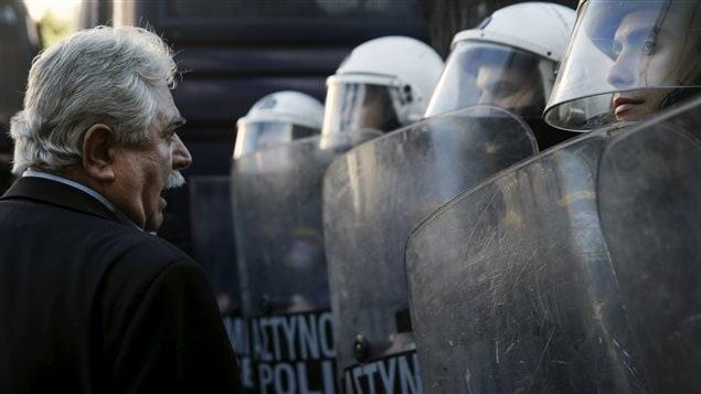 Le député grec Alkis Konstantindis confronte des policiers grecs lors d'une manifestation contre le projet de retraite du gouvernement.