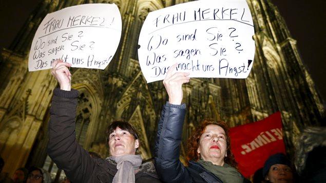 «Madame Merkel, où êtes-vous? Que dites-vous? Cela nous inquiète», peut-on lire sur ses pancartes brandies par deux femmes lors d'une manifestation organisée mardi devant la cathédrale de Cologne.
