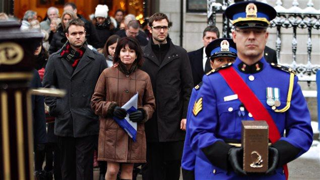 La femme de Jean-Paul L'Allier, Johanne Mongeau, marche derrière l'urne qui contient les cendres de son mari à la fin des funérailles