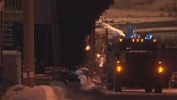 Un policier lance une bombe lacrymogène depuis le toit du véhicule du groupe tactique d'intervention.