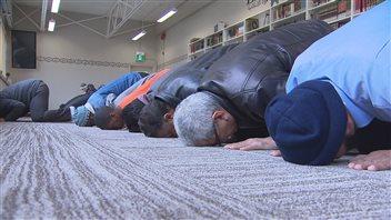 Des hommes prient agenouillés le front collé au sol.