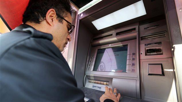 Un Iranien retire de l'argent à un guichet bancaire de Téhéran.