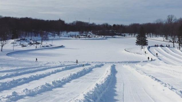 La patinoire naturelle du Lac aux Castors est déserte, de même que les glissades, toutes deux interdites. En arrière plan, les patineurs se massent sur la patinoire artificielle.