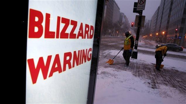 Des travailleurs commencent à nettoyer la neige qui tombe à Washington