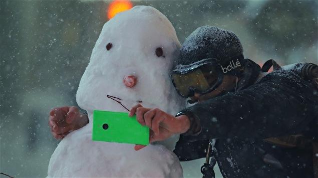 Un homme prend un égoportrait avec un bonhomme de neige à New York