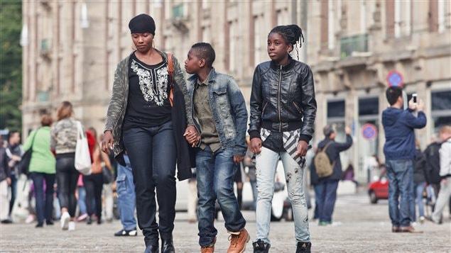 Une famille de touristes déambule tranquillement sur la Place du Dam à Amsterdam.