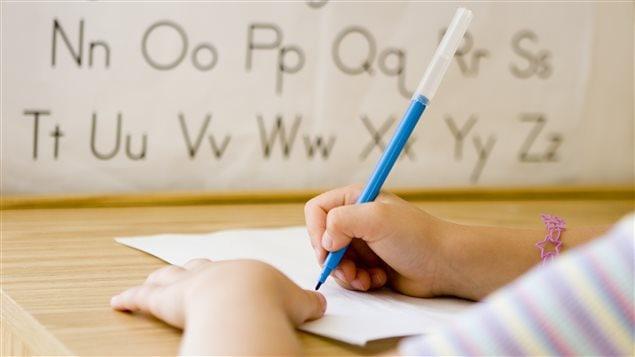 Un enfant écrit sur une feuille à l'école.