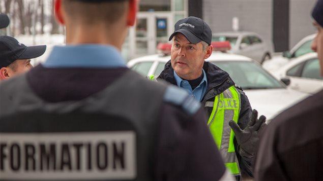 L'instructeur de l'École nationale de police du Québec à Nicolet, Martin Destrempes avec des aspirants policiers en discussion après une simulation.