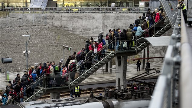 Des migrants font la file à la station de train de Malmo, en Suède.