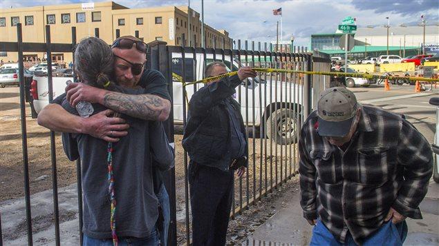 Des hommes s'enlacent pour se réconforter après la fusillade qui a éclaté samedi dans un amphithéâtre de Denver.