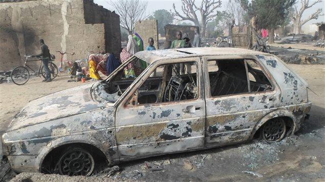 Des enfants se rassemblent près d'une auto détruite par les flammes à la suite d'une attaque du groupe Boko Haram dans la localité de Dalori, au Nigeria.