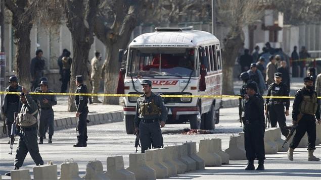 Des policiers afghans montent la garde sur le site d'un attentat suicide.