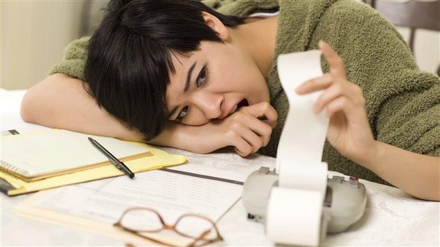 Une femme inquiète fait son budget.