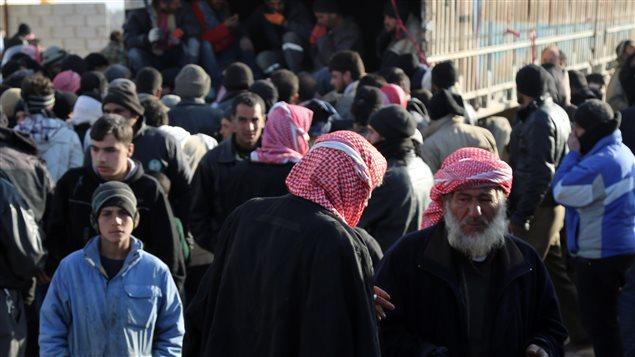 Sur cette photo prise par la Fondation turque pour l'Aide Humanitaire, des Syriens fuyant le conflit à Alep arrivent au poste frontière de Bab el Salam, en Syrie.