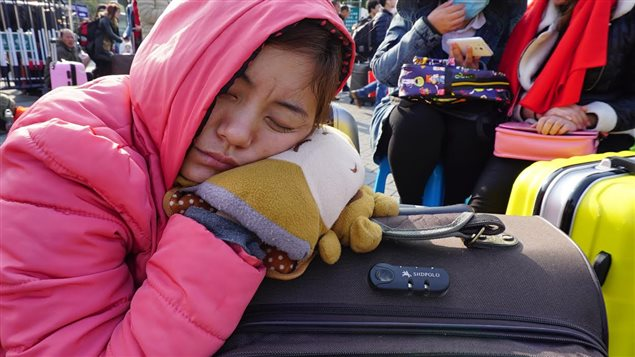 Une jeune femme sommeille en attendant le train vers Hebei.