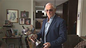 L'ancien joueur des Castors de Sherbrooke Georges Guilbault tient la Coupe Ahearn