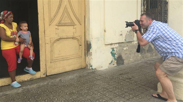 Un touriste américain prend des Cubains en photo.