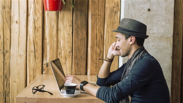 Un jeune homme travaille sur un ordinateur portable.