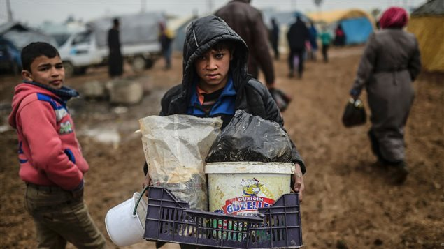 Un enfant transporte quelques effets personnels au camp de Bab Al-Salama, près d'Azaz.