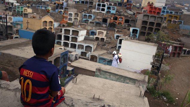 Un garçon observe un agent de santé qui répand des pesticides pour lutter contre le virus Zika dans un cimetière en banlieue de Lima, au Pérou.
