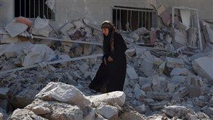 Une femme marche à travers les décombres après des frappes aériennes des forces gouvernementales pro-syrienne à Daël, une ville contrôlée par les rebelles, dans la province de Deraa, en Syrie.