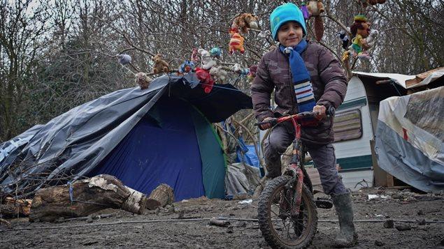 Un jeune réfugié du camp de Grande-Synthe, enfourchant un vélo.