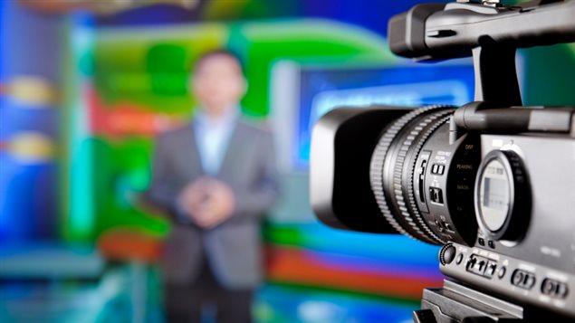 Un homme présente les nouvelles devant une caméra.