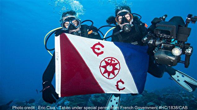 Michel Labrecque et Julie Ouimet présente le drapeau du Explorer Club de New York lors de leur mission au coeur du Pacifique.