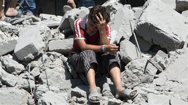 Un jeune syrien pleure parmi les ruines après un tir de missile des forces armées du président Bachar Al-Assad contre un secteur résidentiel de la ville d'Alep, le 21 juillet 2015. Au moins 18 civils ont été tués dans cette attaque.