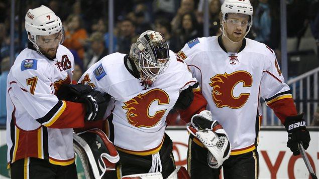 Le gardien des Flames, Karri Ramo, est escorté hors de la patinoire par ses coéquipiers T.J. Brodie et Douggie Hamilton.
