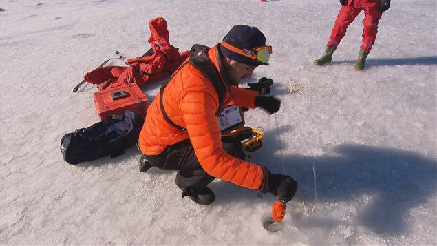 Une sonde est introduite dans un trou pour mesurer les mouvements des vagues.