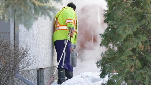 Un employé de la Ville de Winnipeg fait fondre la neige près d'une résidence du croissant Bayne, le 21 février 2016, où les policiers enquêtent sur la mort du jeune Cooper Nemeth, disparu sept jours plus tôt.