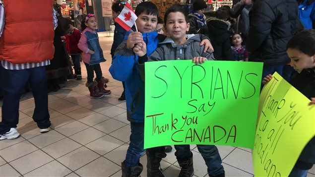 Des réfugiés syriens ont brandi des pancartes faites maison où on peut lire « Les Syriens disent merci au Canada » ou « Merci à tous les Canadiens ».