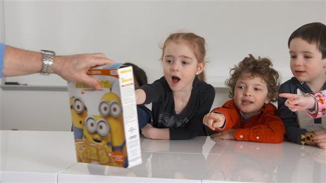 Des enfants réagissent devant une boîte de céréales aux couleurs des Mignons.