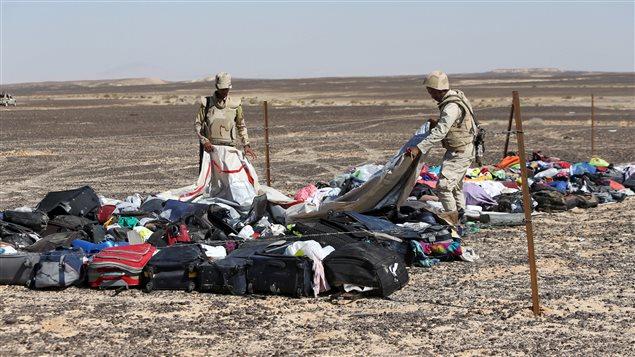 Des soldats égyptiens recueillent les effets des passagers de l'écrasement d'un Airbus dans le désert du Sinaï survenu le 31 octobre 2015.