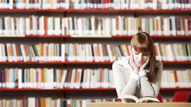 Femme lisant un livre dans une bibliothèque.