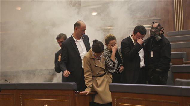 Des membres du Parlement du Kosovo incommodés par du gaz lacrymogène lors de la séance d'élection du président Hashim Thaci.